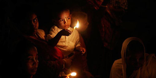 Family offering candle-light to Krishna during Karttika